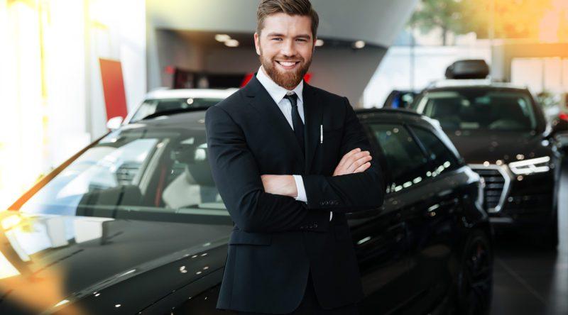 Automobilkaufmann mit stabiler Pose und verschränkten Armen und einem lächeln in einer Autohaus.