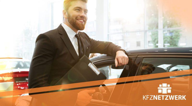Automobilkaufmann mit Akten an der Hand und an einem Fahrzeug angelehnt. Orangefahriger Streifen mit KFZ-NETZWERK Logo