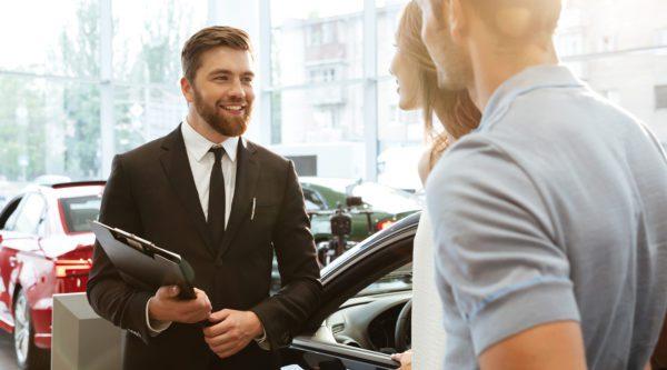 Ein Automobilkaufmann Verhandelt mit einer Kundin und einem Kunden in einer Autogalerie.