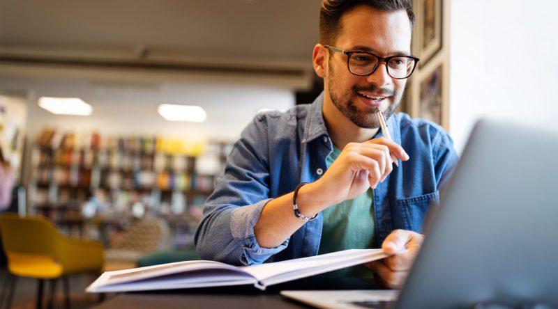Automobil-Serviceberater beim lernen in einer Bibliothek mit seinem Laptop.