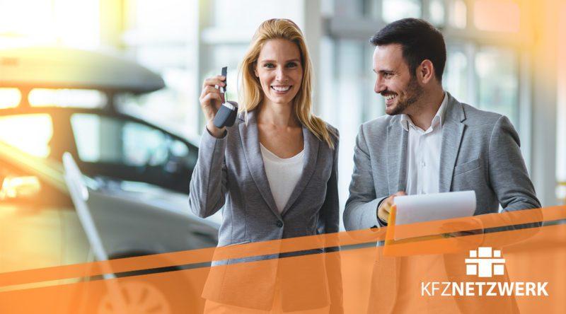 Kfz-Serviceberater übergibt Autoschlüssel un Kundin in einer Autogalerie. Zu Sehen ist auch auf dem Bild das Logo von KFZ-NETZWERK