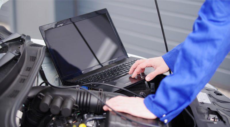 Kfz-Meister arbeiten selbst praktisch in der Werkstatt mit und misst mit seinem Laptop die Werte vom Fahrzeug ab.