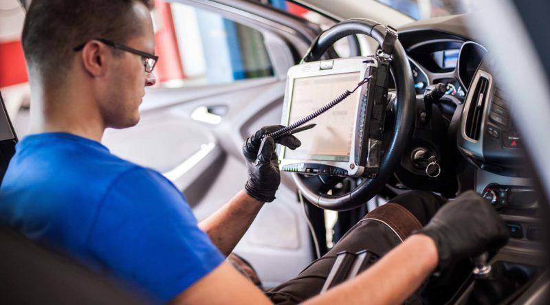 Kfz-Mechatroniker beim Abmessen elektronischer Sicherheitsprüfungen und das Erfassen elektronischer Messwerte an einem Fahrzeug im Innenraum.