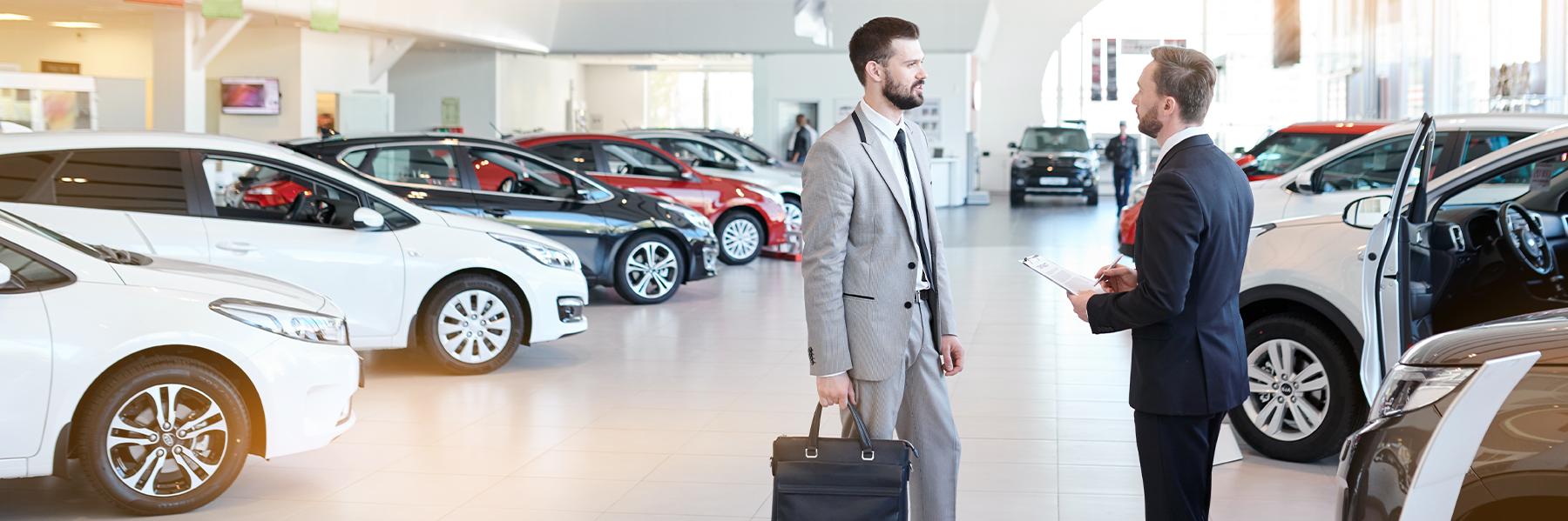 Autoverkäufer im Gespräch mit Kfz Disponenten im Ausstellungsraum